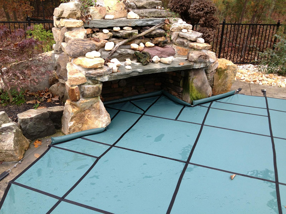 Safety Pool Cover Installation with Rock Waterfall